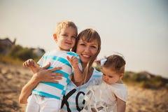 关闭一起拥抱她的小孩子的年轻微笑的母亲,获得乐趣在海滩,愉快的生活方式家庭观念 免版税库存图片