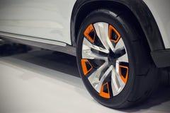 关闭一辆汽车的后面轮子在白色地板上的 免版税库存图片
