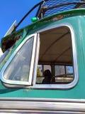 关闭一辆老绿色生锈的葡萄酒公共汽车的开放侧面窗 库存照片