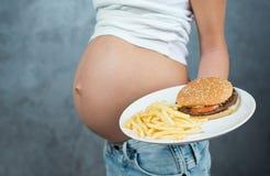 关闭一逗人喜爱的怀孕的腹部和速食 免版税库存照片
