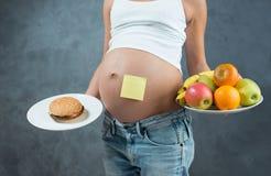 关闭一逗人喜爱的怀孕的腹部肚子和健康不健康 免版税库存照片