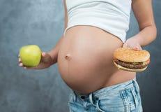 关闭一逗人喜爱的怀孕的腹部肚子和健康不健康 库存照片