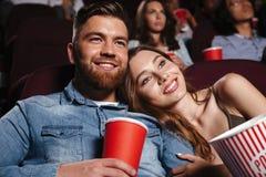 关闭一部微笑的年轻夫妇观看的电影 免版税库存图片