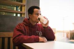 关闭一份年轻人放松的和饮用的咖啡的画象在城市 免版税库存图片
