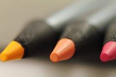 关闭三支橙黄色颜色铅笔 免版税库存图片