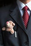 关闭与保留小玩具熊的典雅的时髦的商人在他的乳房衣服夹克口袋 正式交涉 库存照片