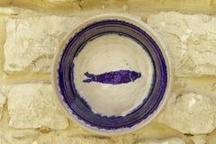 关闭与在一个石墙上显示的一条紫色鱼的瓦器陶器在西西里岛 库存图片