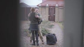 关闭与大袋子拥抱与他的在房子前面的妻子的军事的年轻战士 一个人从回来 影视素材