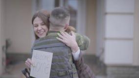 关闭与大袋子拥抱与他的妻子的军事的年轻战士拿着与受欢迎的家庭署名的纸 影视素材