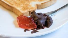 关闭与巧克力传播的鲜美面包多士和草莓酱 免版税库存照片