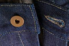 关闭与开放按钮的牛仔裤片段 棉花牛仔布详细资料织品牛仔裤纹理 免版税库存照片