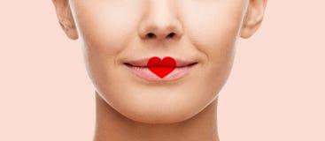 关闭与心脏形状的妇女面孔在嘴唇 免版税库存照片