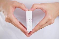 关闭与感觉幸福的爱妇女的妊娠试验 免版税库存照片