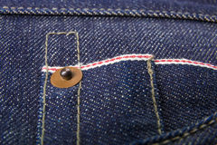 关闭与按钮的牛仔裤片段 棉花牛仔布详细资料织品牛仔裤纹理 免版税库存照片