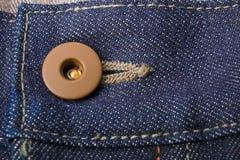 关闭与按钮的牛仔裤片段 棉花牛仔布详细资料织品牛仔裤纹理 库存图片