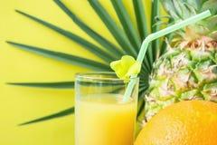 关闭与新近地被按的菠萝橙色椰子汁秸杆和小花的高玻璃 在黄色的圆的棕榈树叶子 免版税库存照片
