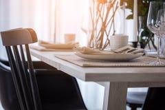 关闭与木桌和盘集合inte的好的用餐的椅子 免版税库存照片