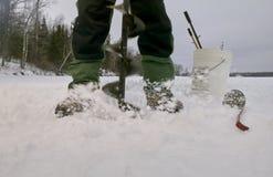 关闭与木钻的冰渔夫钻孔 免版税图库摄影