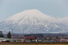 关闭与村庄的登上Yotei不活泼的stratovolcano脚小山和黄色草的在地面上在冬天在北海道 免版税库存照片