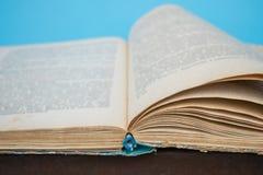 关闭与模糊的文本的被打开的葡萄酒减速火箭的书页edu的 库存照片