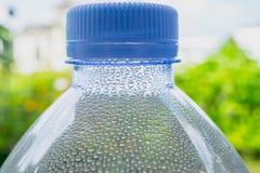 关闭与水下落的瓶颈塑料在绿色自然背景 图库摄影
