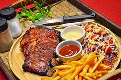 关闭与法语油煎的和沙拉的BBQ肋骨烤牛排集合在竹盘子背景 免版税图库摄影