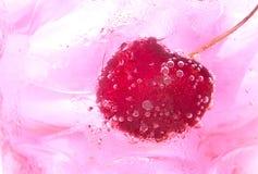 关闭与泡影的樱桃在与冰块的桃红色鸡尾酒 免版税库存照片