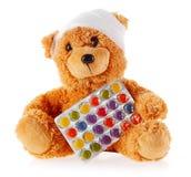 关闭与片剂箔的被包扎的玩具熊  免版税图库摄影