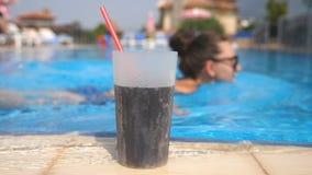 关闭与站立在水池附近的秸杆的刷新的鸡尾酒 太阳镜的少女游泳在玻璃背景的  股票录像