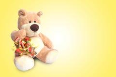 关闭与箱子的玩具熊在黄色背景 图库摄影