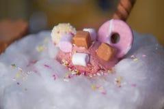 关闭与糖甜白色糖果绣花丝绒的食物摄影充满草莓桃红色冰淇凌和乳脂软糖片 免版税库存图片