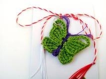 关闭与红色和白色串的一只被编织的蝴蝶 免版税库存照片