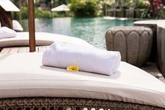 关闭与羽毛赤素馨花的毛巾在轻便折叠躺椅在手段水池 可视巴厘岛美丽的印度尼西亚海岛kuta人连续形状日落的城镇 免版税图库摄影