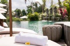 关闭与羽毛赤素馨花的毛巾在轻便折叠躺椅在手段水池 可视巴厘岛美丽的印度尼西亚海岛kuta人连续形状日落的城镇 库存照片