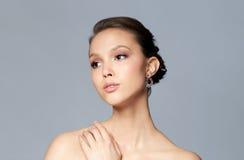 关闭与耳环的美丽的妇女面孔 免版税图库摄影