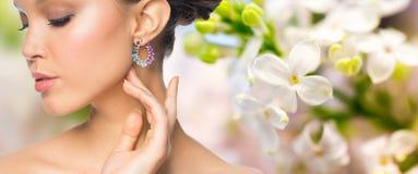 关闭与耳环的美丽的妇女面孔 免版税库存照片