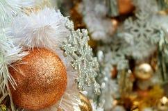关闭与被弄脏的银色闪烁雪花和另一件装饰品的桃红色金子铺砂机球形的圣诞节装饰品 库存图片