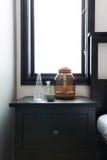 关闭与装饰品和明亮的窗口behin的床头柜 图库摄影