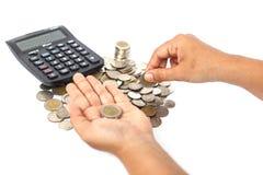 关闭与计算器的硬币在白色b隔绝的手计数 免版税库存图片