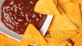 关闭与辣调味汁的转动的烤干酪辣味玉米片芯片 股票视频