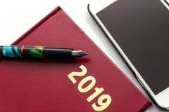关闭与钢笔的2019红色皮革diarys在白色背景 免版税图库摄影
