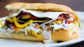 关闭与马约角、葱,胡椒和更多的一个蛋潜水艇三明治 库存照片