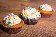 关闭与黄油奶油和cinnam的鲜美五颜六色的杯形蛋糕 免版税图库摄影