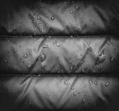 关闭与水滴的蓝色防水雨夹克织品,渐晕作用 免版税库存图片