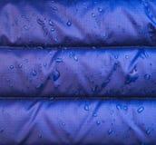 关闭与水滴的蓝色防水雨夹克织品 库存照片