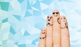 关闭与兴高采烈的面孔的四个手指家庭 免版税库存图片