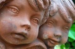 关闭两个古色古香的黏土天使小雕象 免版税库存照片