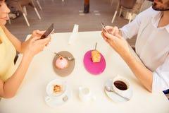 关闭两个年轻恋人播种的照片,坐在咖啡馆和 库存照片