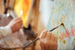 关闭两位艺术家递与刷子的绘画图片 免版税图库摄影