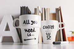 关闭两有diy装饰的加奶咖啡杯子 免版税库存照片